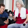 Stock Photo: Trainer instructing a senior woman in the gym