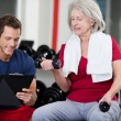 trainer instrueren een senior vrouw in de sportschool — Stockfoto