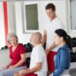 Stock Photo: Trainer correcting posture of elderly man