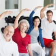 Stock Photo: Group of people doing aerobics at gym