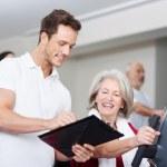 trainer stimuleren een senior vrouw op de sportschool — Foto de Stock