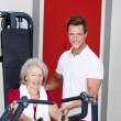 Trainer Assisting Senior Woman Using Rowing Machine — ストック写真
