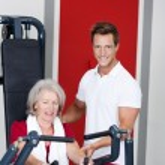treinador auxiliar sênior mulher usando a máquina de remo — Foto Stock