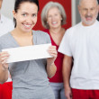 Woman Holding Blank Paper With Family In Background At Gym — Stock Photo