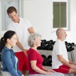 Stock Photo: Instructor Assisting Senior Woman Sitting On Fitness Ball At Gy