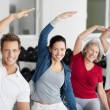 Family Doing Stretching Exercise In Gym — Stock Photo