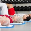 Family Exercising While Lying On Mat At Gym — Stock Photo
