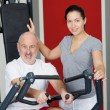Female Instructor With Senior Man Using Rowing Machine In Gym — ストック写真