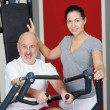 Female Instructor With Senior Man Using Rowing Machine In Gym — Foto de Stock