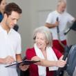 instrutor explicando o cronograma para mulher sênior no ginásio — Foto Stock