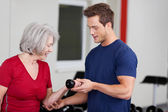 Male gym trainer instructing an elderly woman — Stock Photo