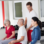 Trainer correcting the posture of an elderly man — Stock Photo