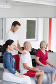 Trainer helping a senior man at the gym — Stock Photo