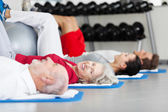 Elderly woman working out in a gym — Stock Photo