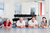 Family Lying On Mat In Gym — Stock Photo
