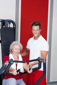 Trainer Assisting Senior Woman Using Rowing Machine — Stock Photo
