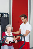 Senior Woman Being Assisted By Trainer In Using Rowing Machine — Stock Photo