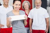 žena držící prázdný papír s rodinou v pozadí v tělocvičně — Stock fotografie