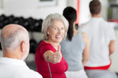 Woman Gesturing Thumbs Up Sign With Family Sitting In Gym — Stock Photo