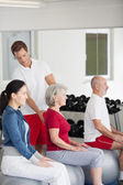 Instructor Assisting Senior Woman Sitting On Fitness Ball At Gy — Stock Photo