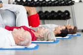 Familie uitoefening liggend op de mat te plaatsen bij gym — Stockfoto