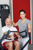 Female Instructor With Senior Man Using Rowing Machine In Gym — Stock Photo