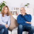 Couple Smiling While Sitting On Sofa At Home — Stock Photo