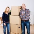 Confident Couple Standing By Stacked Cardboard Boxes At New Home — Stock Photo