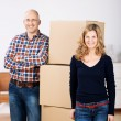 Couple standing with boxes in their new house — Stockfoto