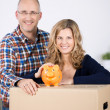 Couple With Cardboard Box And Piggybank At New Home — Stock Photo