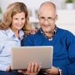Happy couple reading information on their laptop — Stock Photo