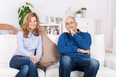 Couple Smiling While Sitting On Sofa At Home — Stok fotoğraf