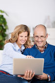 Happy couple sharing a laptop computer — Stock Photo