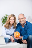 Couple With Laptop And Piggybank Making Savings Plan At Table — Stock Photo