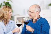 Couple Toasting Red Wineglasses While Looking At Each Other — Stock Photo