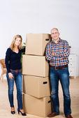 уверен пара, стоя у сложены в картонные коробки в новом доме — Стоковое фото