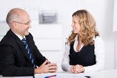 Businesspeople Conversing While Looking At Each Other At Desk — Stock Photo