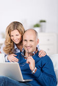 Married couple relaxing with a laptop — Stock Photo