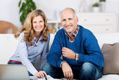 Couple with a laptop and paperwork at home — Stock Photo