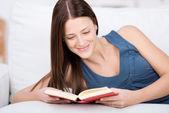 Woman enjoying her book at home — ストック写真