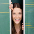 Smiling young female behind two panels — Stock Photo