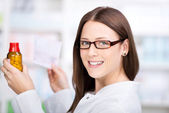 Smiling pharmacist fulfilling a prescription — Stock Photo