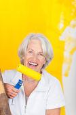 äldre kvinna håller rullen mot gula målad vägg — Stockfoto