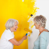 Senior Women Painting Wall With Yellow Paint — Stock Photo