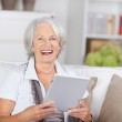 Laughing beautiful senior with a tablet-pc — Stock Photo