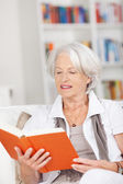 Senior woman relaxing and reading a book — Stock Photo