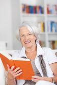 Senior Woman Holding Book While Sitting On Sofa — Stock Photo