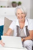 Senior Woman Using Laptop While Sitting On Sofa — Stock Photo