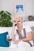 Senior Woman Conversing On Cordless Phone While Sitting On Sofa — Stock Photo