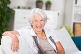 äldre kvinna som sitter på soffan hemma — Stockfoto